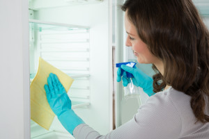 women cleaning freezer